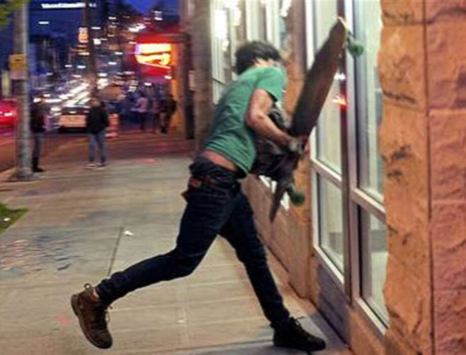 Police also have video of this man throwing his skateboard through a Capitol Hill business window. Photo: SPD