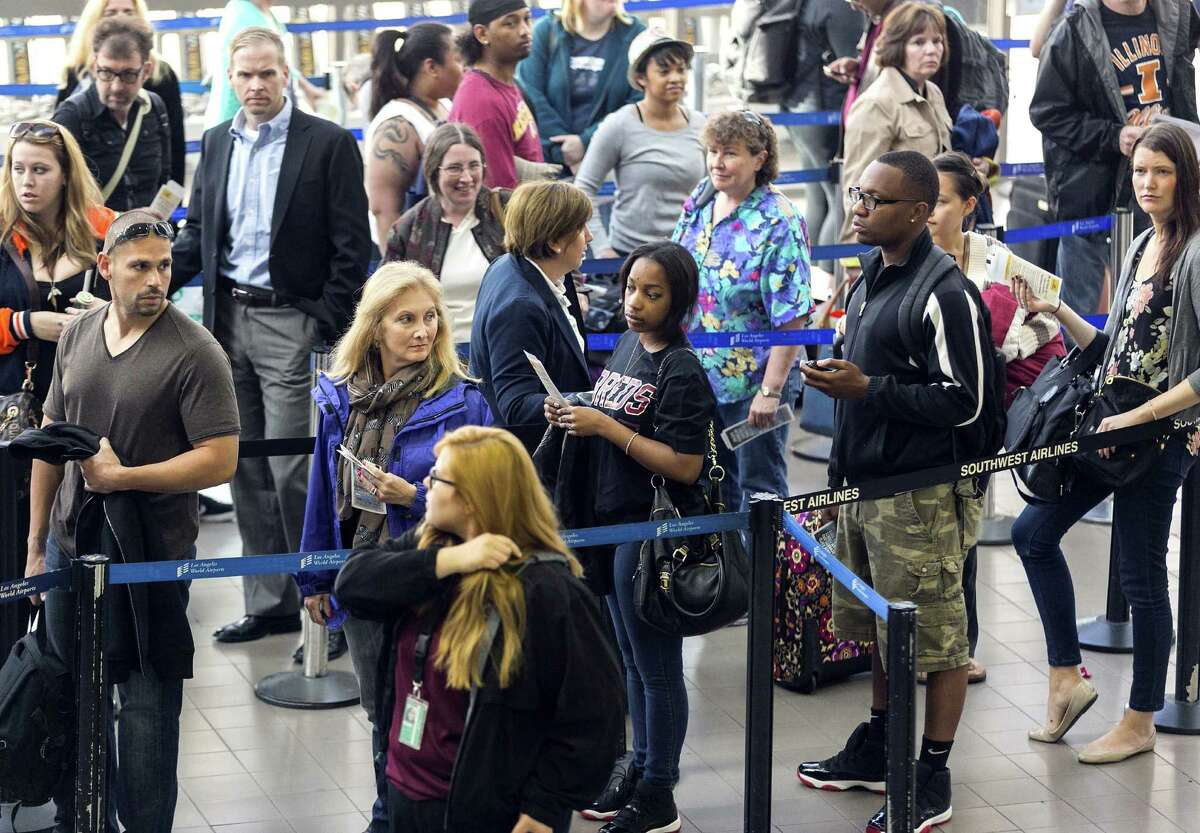 Travelers stand in line last month at Los Angeles International Airport. A summer travel forecast bodes well for airlines, as more people are expected to fly, , an industry group said.