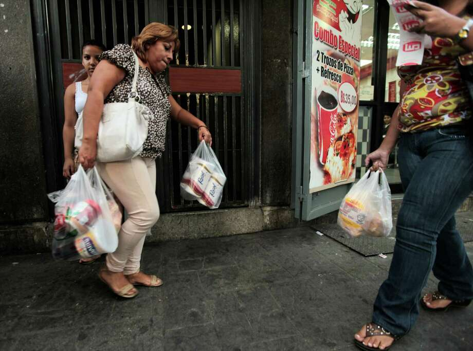 A customer leaves a private market in Caracas on Wednesday carrying scarce toilet paper. The government says 50 million rolls of tissue are on the way. Photo: Fernando Llano, STF / AP