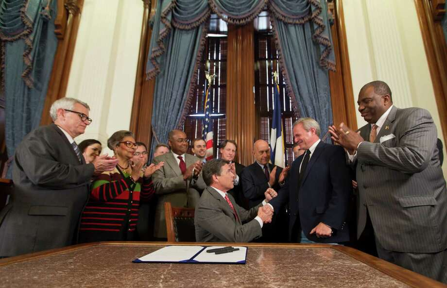 Gov. Rick Perry presents Michael Morton with a pen Thursday in Austin after signing the Michael Morton Act into law. Photo: Ricardo Brazziell, Photojournalist / AUSTIN AMERICAN-STATESMAN