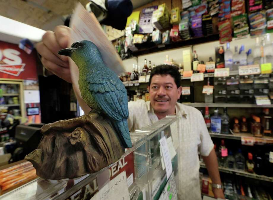 "Ronald Marin rubs his lottery tickets on the wings of a ""bluebird"" statue for good luck at the Bluebird Liquor store in Hawthorne, Calif., on Thursday. The next drawing will be held Saturday. Photo: Damian Dovarganes, STF / AP"