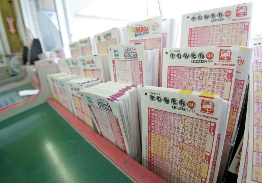 Powerball tickets, right, along with other lotto tickets are seen Thursday, May 16, 2013, at a convenience store in Orlando, Fla.  The prize estimated around $475 million is the third largest in lottery history, and the winning numbers will be drawn on Saturday.(AP Photo/John Raoux) Photo: John Raoux, STF / AP