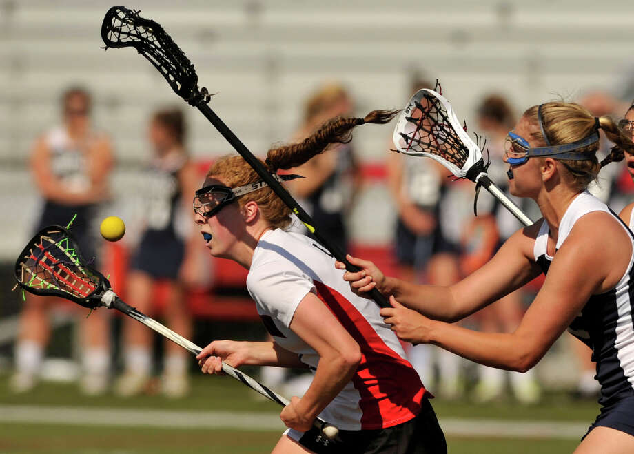 Staples' Jenna McNicholas forces the ball from the possession of Elizabeth Miller, of New Canaan, during their FCIAC quarterfinal game at New Canaan High School on Thursday, May 16, 2013. New Canaan won, 12-5. Photo: Jason Rearick / Stamford Advocate