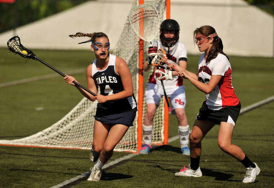 Staples' Jenna McNicholas turns away from the goal with the help of New Canaan's Olivia Hompe during their FCIAC quarterfinal game at New Canaan High School on Thursday, May 16, 2013. New Canaan won, 12-5. Photo: Jason Rearick / Stamford Advocate