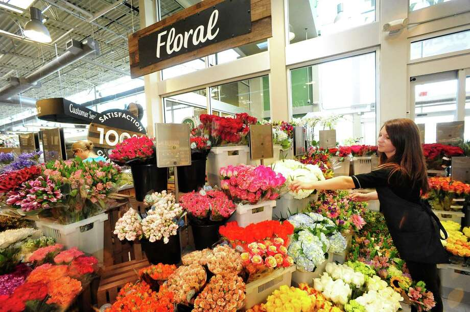 Lindsay Podesta puts finishing touches on the floral display as the new Whole Foods store prepares to open in Danbury, Conn. Thursday, May 16, 2013. Photo: Michael Duffy / The News-Times