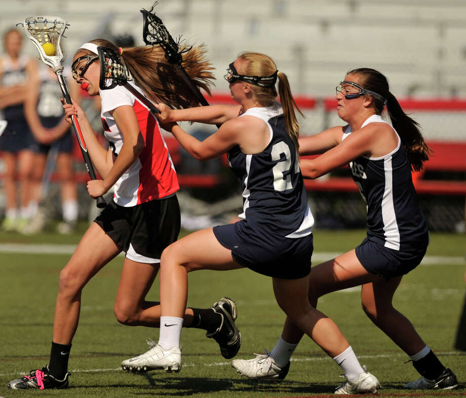 New Canaan's Kathleen DeMarino is pressured by Staples' Nicole Williams, center, and Amelia Heisler during their FCIAC quarterfinal game at New Canaan High School on Thursday, May 16, 2013. New Canaan won, 12-5. Photo: Jason Rearick / Stamford Advocate
