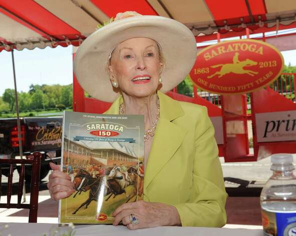 Marylou Whitney holds a book celebrating the 150 years of the Saratoga Race Course during a press conference at the track on Thursday, May 16, 2013 in Saratoga Springs, N.Y. Committee Honorary Chairs and Chairman held the news conference to announce final, detailed plans for Saratoga?s five-month-long celebration. (Lori Van Buren / Times Union) Photo: Lori Van Buren / 10022450A