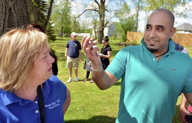 Building owner Luann Feiden Akins, left, and convenience store operator Muhammed Shahvaz watch as firefighters battle a fire at the Handy Andy market and Vintage pizzaria on Rt. 155 in Colonie, NY Thursday May 16, 2013.  (John Carl D'Annibale / Times Union) Photo: John Carl D'Annibale
