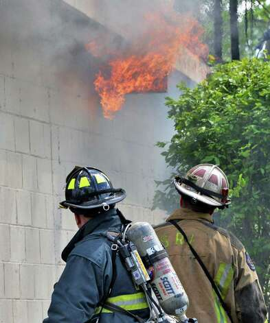 Firefighters watch as flames break out again as they battle a stubborn fire at the Handy Andy market and Vintage Pizza on Rt. 155 in Colonie, NY Thursday May 16, 2013.  (John Carl D'Annibale / Times Union) Photo: John Carl D'Annibale