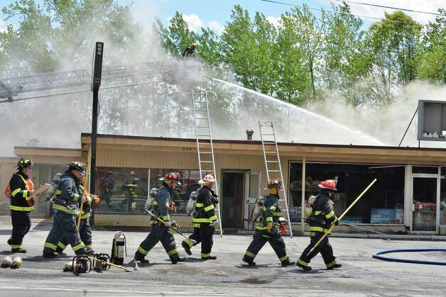 Firefighters march back in to battle a stubborn fire at the Handy Andy market and Vintage Pizza on Rt. 155 in Colonie, NY Thursday May 16, 2013.  (John Carl D'Annibale / Times Union) Photo: John Carl D'Annibale