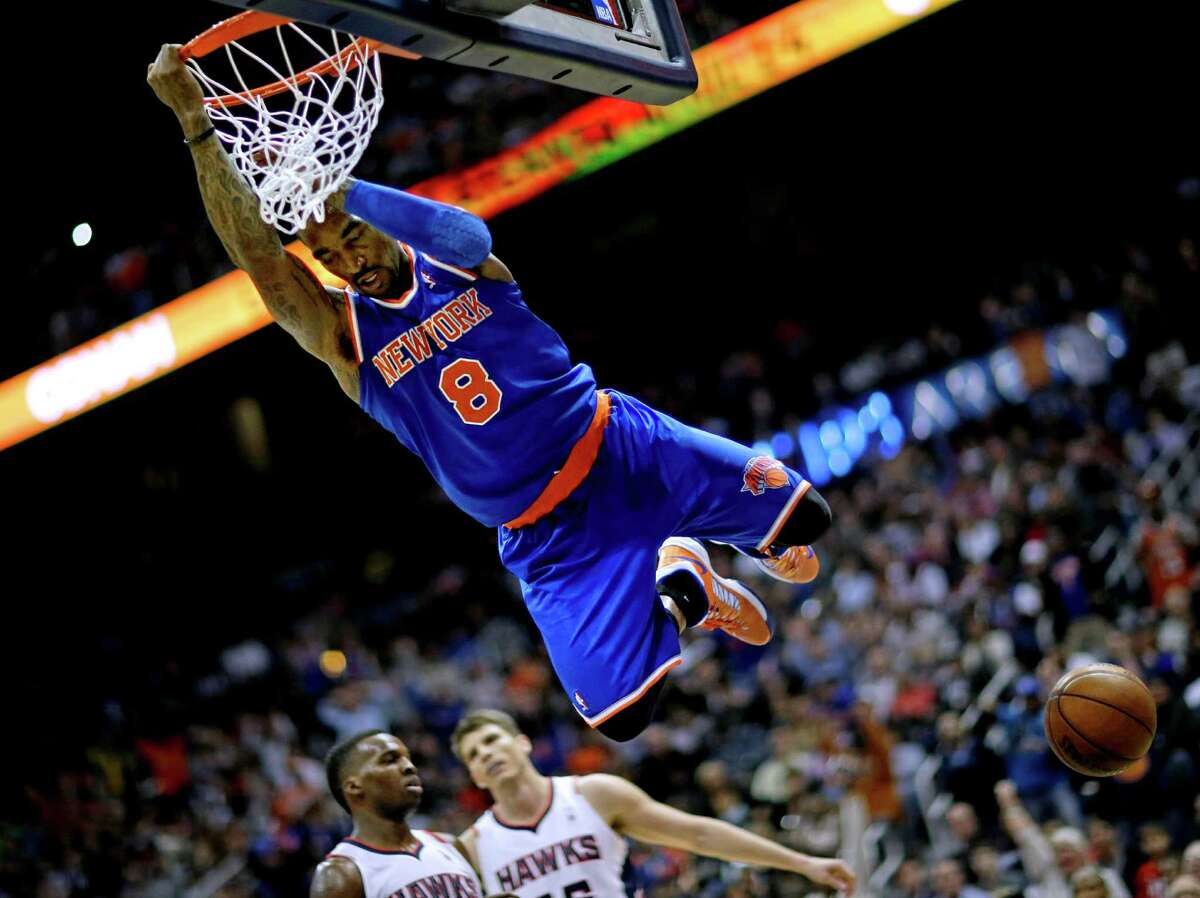 FILE - In this April 3, 2013 file photo, New York Knicks' J.R. Smith hangs from the rim after dunking the ball in the fourth quarter of an NBA basketball game against the Atlanta Hawks in Atlanta. A person with knowledge of the voting results tells The Associated Press that J.R. Smith has won the NBA's Sixth Man of the Year award. (AP Photo/David Goldman, File)