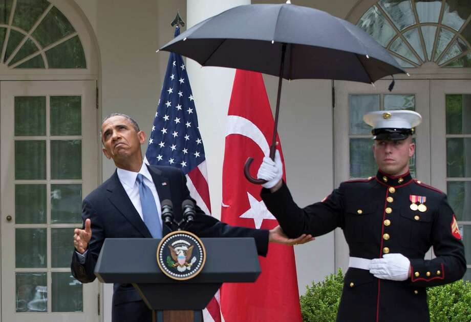President Barack Obama leans out from under an umbrella to check if it's still raining, during a joint news conference with Turkish Prime Minister Recep Tayyip Erdogan, Thursday, May 16, 2013, in the Rose Garden of the White House in Washington. (AP Photo/Jacquelyn Martin) Photo: Jacquelyn Martin