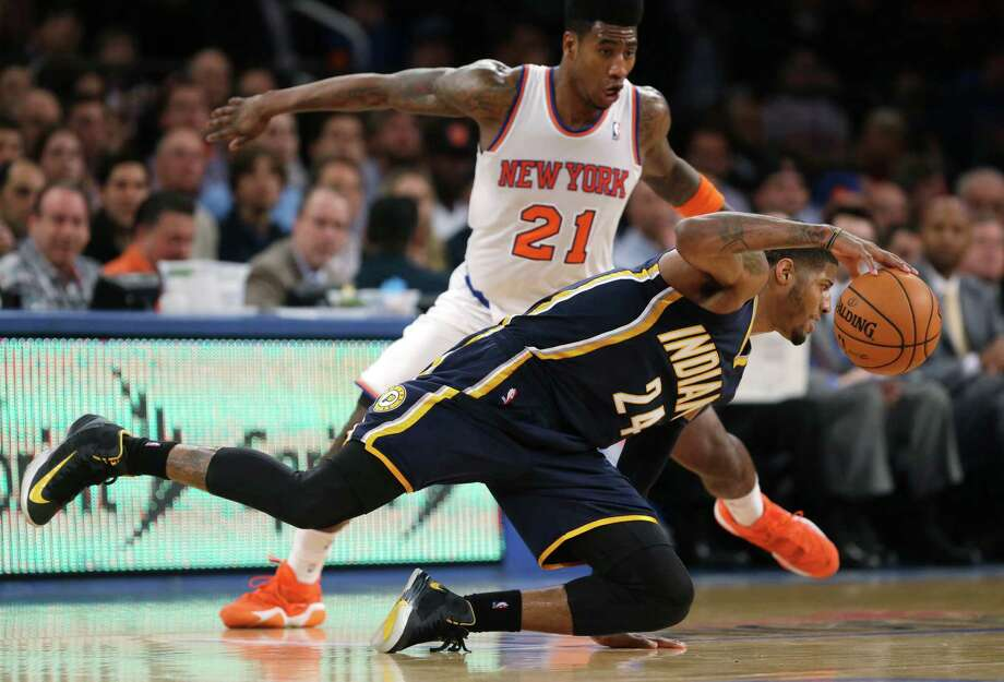 Indiana Pacers' Paul George (24) loses his balance as New York Knicks' Iman Shumpert (21) defends in the second half of Game 5 of an Eastern Conference semifinal in the NBA basketball playoffs, at Madison Square Garden in New York, Thursday, May 16, 2013. Photo: Julio Cortez