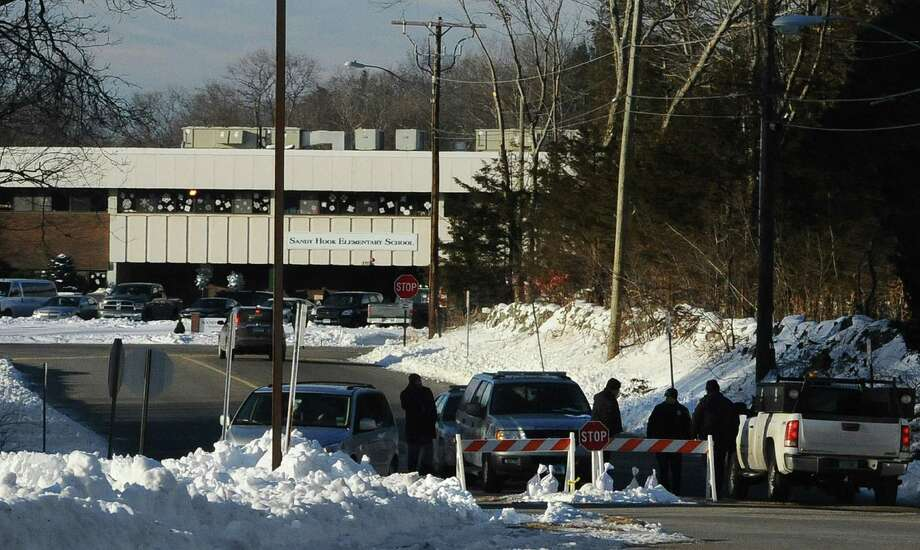 A police road block is at the entrance to the new Sandy Hook Elementary School on the first day of classes in Monroe, Conn., Thursday, Jan. 3, 2013. The school, formerly known as Chalk Hill School, was overhauled specially for the students from the Sandy Hook School shooting in Newtown, in the neighboring town of Monroe, Conn. (AP Photo/Jessica Hill) Photo: Jessica Hill, ASSOCIATED PRESS / A2013