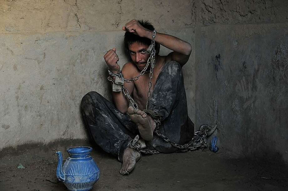 A mentally ill Afghan patient sits chained to a wall at the Mia Ali Baba holy shrine in the village of Samar Khel on the outskirts of Jalalabad on May 16, 2013. At the Mia Ali Baba sanctuary the patients, presumed to be possessed by jinns (demons), are chained by the wrist inside, or in the open air  to a tree, for 40 days.  Photo: Noorullah Shirzada, AFP/Getty Images