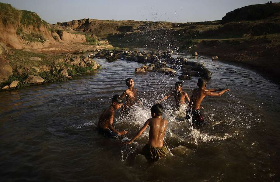 Following their daily work at a wholesale fruit and vegetable market, Pakistani boys cool off in a polluted stream next to water buffaloes as the temperature rises on the outskirts of Islamabad, Pakistan, Thursday, May 16, 2013.  Photo: Muhammed Muheisen, Associated Press