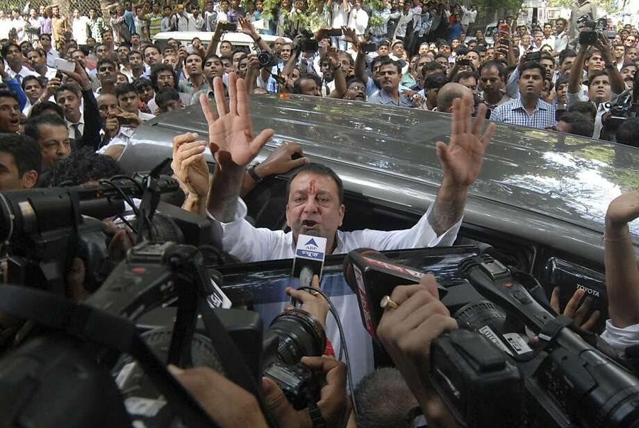 Bollywood star Sanjay Dutt, gestures to the media as he arrives at a court in Mumbai, India, Thursday, May 16, 2013. Dutt has been sentenced to five years in prison for a 1993 weapons conviction linked to a deadly terror attack in Mumbai that killed 257 people. The 53-year-old actor served 18 months in jail before being released on bail in 2007 pending an appeal. The Supreme Court reduced his prison sentence to five years from the six-year term initially handed down.  Photo: Rajanish Kakade, Associated Press