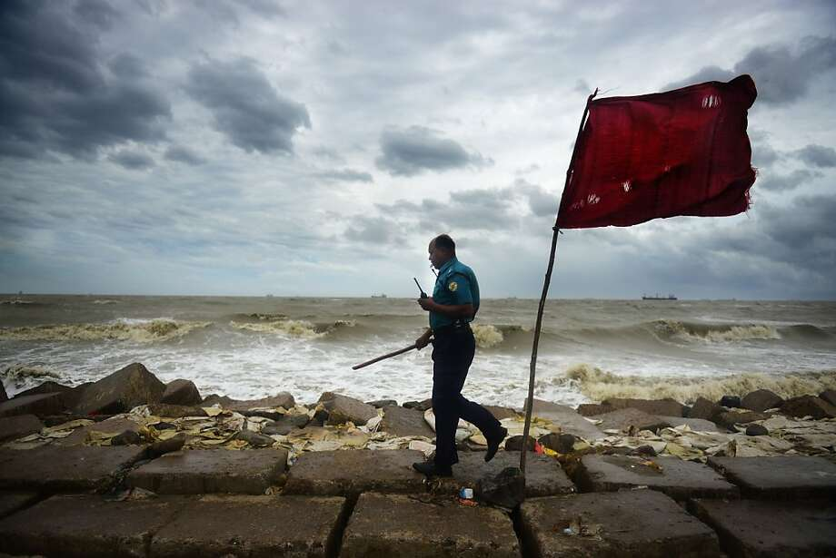 A Bangladeshi police official evacuates the beach for safety while  Cyclone Mahasen heads towards landfall in Chittagong on May 16, 2013. A cyclone slammed into the Bangladeshi coast as a million people hunkered down in evacuation shelters, including in a region of Myanmar torn by communal unrest.  Photo: Munir Uz Zaman, AFP/Getty Images