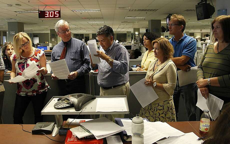 Sunday Editor Sergio Bustos, center, reads from his budget during the Miami Herald's last daily three o'clock meeting in the newsroom at One Herald Plaza in Miami on Thursday, May 16, 2013.  The Miami Herald began their moving process as it relocates to its new office in Doral, Fla.  Photo: Carl Juste, Associated Press