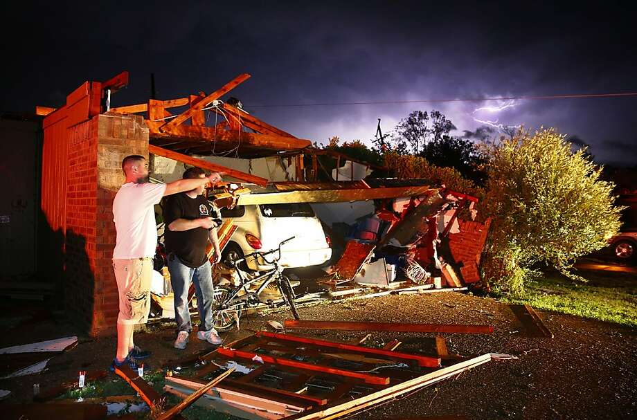 Derrek Grisham, left, points out neighborhood damage to storm chaser Travis Schafer after a tornado damaged his mother's house on Hyde Park Lane at Country Club Rd. in Cleburne, Texas,Wednesday night, May 15, 2013. Cleburne Mayor Scott Cain early Thursday declared a local disaster as schools canceled classes amid the destruction.  Photo: Tom Fox, Associated Press