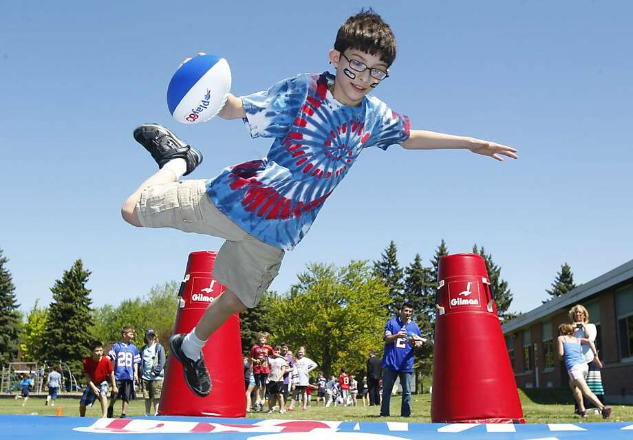 Gabriel Waddell, 10, soars through the air as he participates in  the NFL's Play 60 program at the Forest Elementary School in Amherst, N.Y., Thursday, May 16, 2013. Several Buffalo Bills were on hand and participated.  Photo: Harry Scull Jr., Associated Press