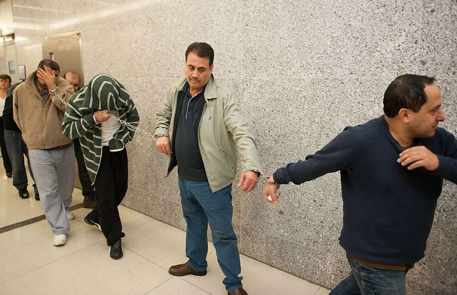 Suspects in a smuggling ring that made a fortune selling more than a million of cartons of untaxed cigarettes in New York, including, from left, Yousseff Odeh; Murad Bishrat, Saad Badr and Izzat Nimer, are led chained together through the corridors of the Federal Courthouse in the Brooklyn Borough of New York, Thursday, May 16, 2013. Authorities say the smuggling ring may have funneled some of the illicit proceeds to terrorist groups.  Photo: Craig Warga, Associated Press