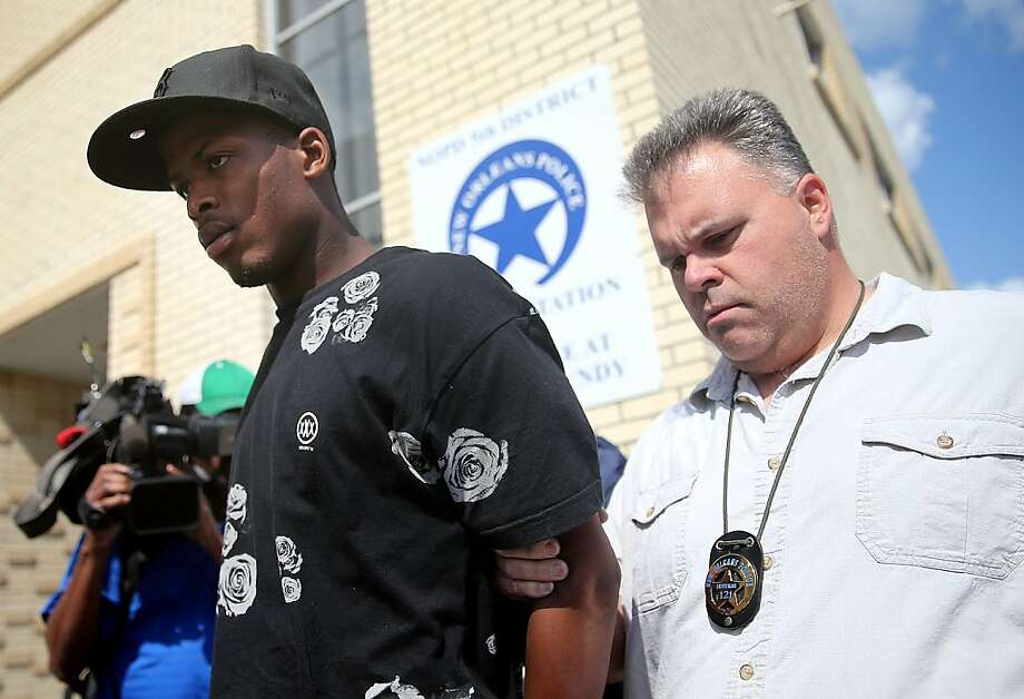 Shawn Scott, left, who with his younger brother Akien is accused of the Mother's Day second-line shooting which injured 20 people, is taken from the 5th District Police Station to Orleans Parish Prison in New Orleans on Thursday, May 16, 2013.  Photo: MICHAEL DeMOCKER, Associated Press