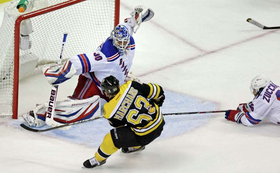 Boston Bruins left wing Brad Marchand (63) beats New York Rangers goalie Henrik Lundqvist (30) for the game-winning goal during overtime in Game 1 of an NHL hockey playoffs Eastern Conference semifinal in Boston, Thursday, May 16, 2013. Rangers right wing Mats Zuccarello (36), right, looks on. (AP Photo/Charles Krupa) Photo: Charles Krupa