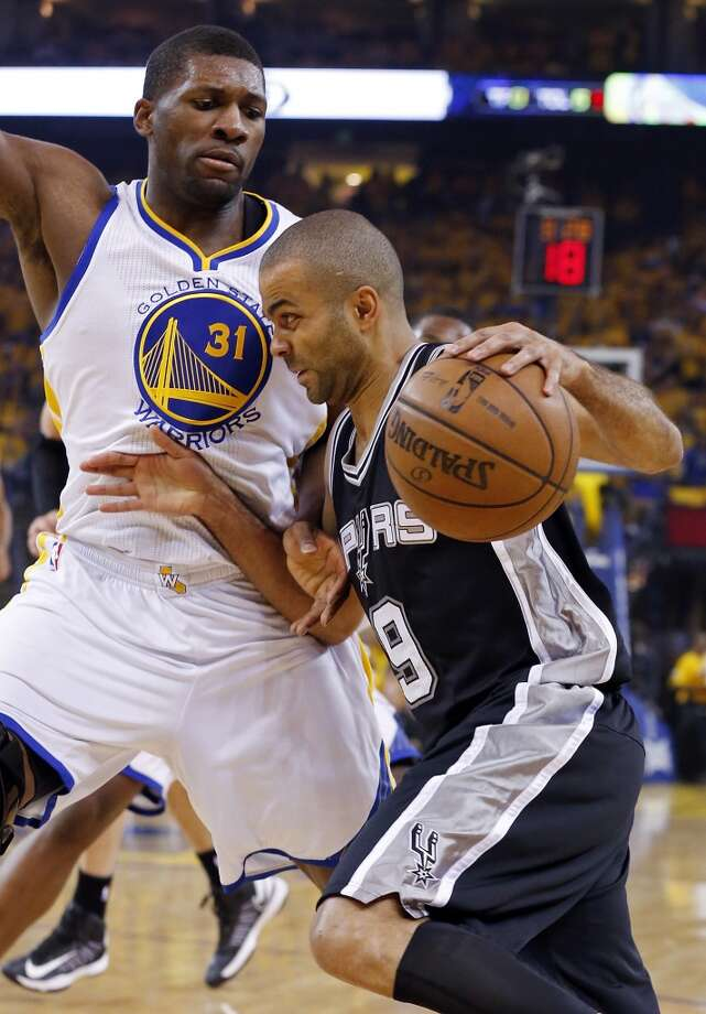 The Spurs' Tony Parker looks for room around the Warriors' Festus Ezeli during first half action of Game 6 in the NBA Western Conference semifinals Thursday May 16, 2013 at Oracle Arena in Oakland, CA.