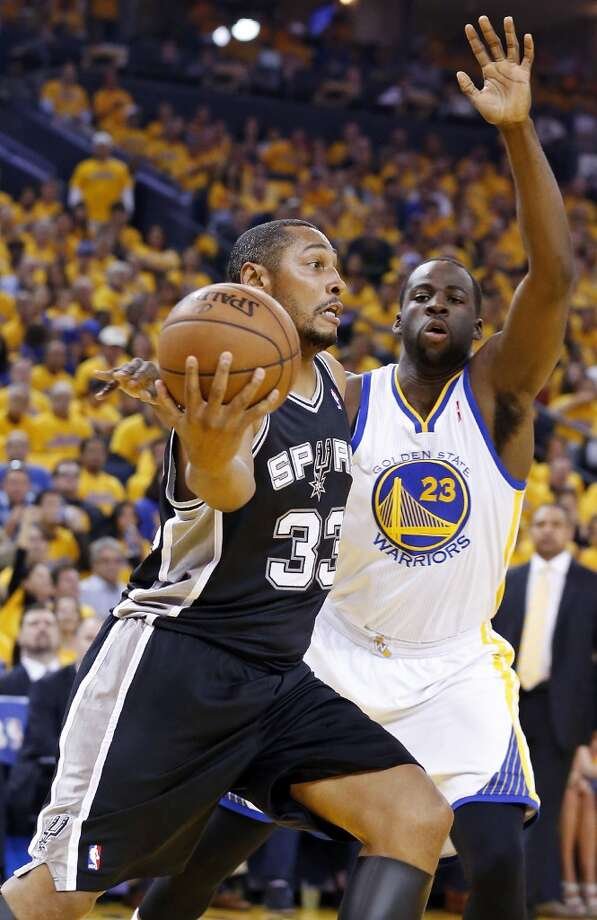 The  Spurs' Boris Diaw passes around the  Warriors' Draymond Green during first half action of Game 6 in the NBA Western Conference semifinals Thursday May 16, 2013 at Oracle Arena in Oakland, CA.