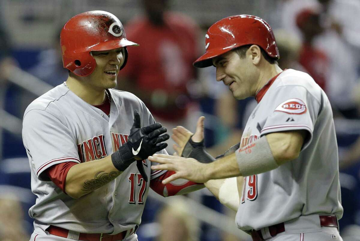 The Reds' Shin-Soo Choo (left) and Joey Votto exult after scoring on a 10th-inning double by Jay Bruce.