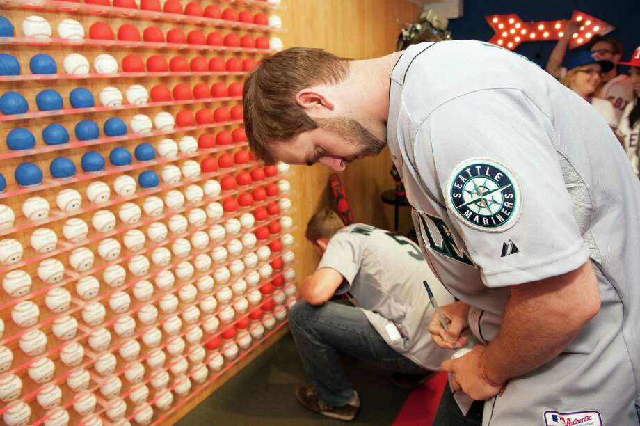 Lucas Luetge of the Seattle Mariners signs the Rawlings Ball Wall. Photo: Thomas Levinson, MLB Photos Via Getty Images / 2013 Major League Baseball Photos