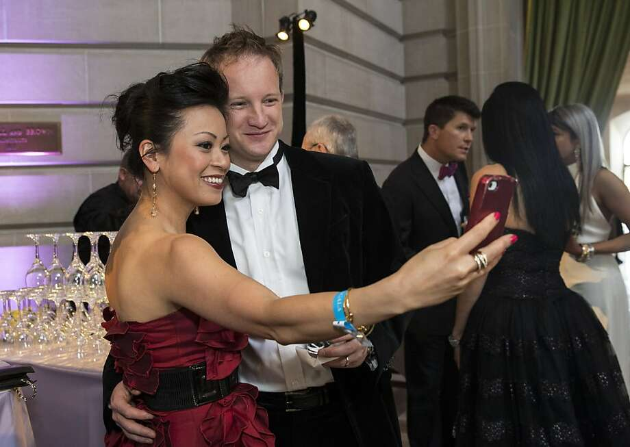 Denise Tran (left) snaps a photo of herself with Jesse Watson while attending the cocktail hour at the San Francisco Symphony's inaugural Spring Gala at City Hall in San Francisco, Calif., on Thursday, May 16, 2013. Photo: Laura Morton, Special To The Chronicle