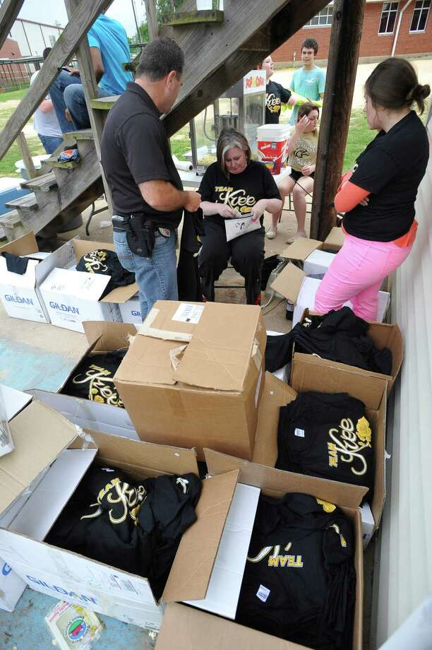 Amy Bythewood, center, surrounded by various Kree T-Shirts in several sizes, tries to help another customer. The City of Woodville hosted a Kree Harrison watch party Thursday night at the Joe Wheat Dogwood Amphitheater in downtown Woodville. Upwards of 150 people sat on concrete, chairs, and blankets to enjoy the two hour season finale of American Idol  Dave Ryan/The Enterprise Photo: Dave Ryan