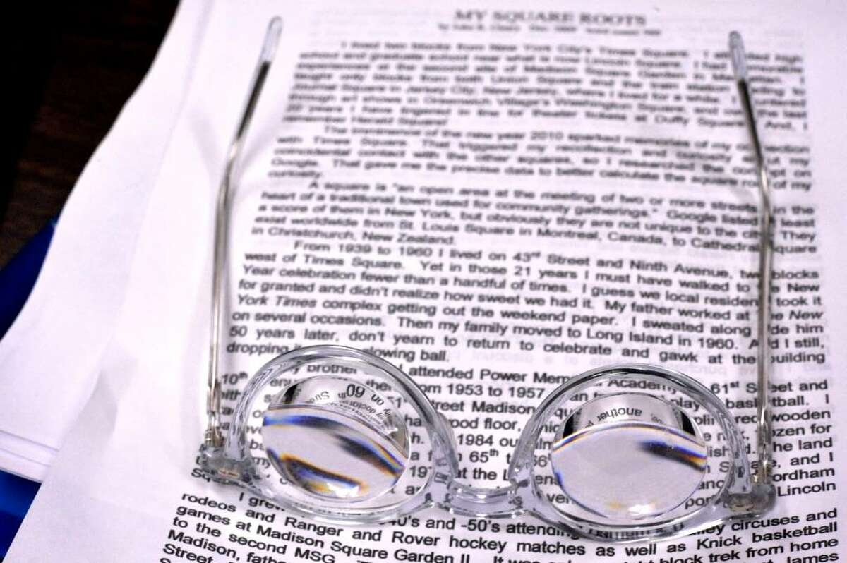 John Contrata's glasses, 81, rest on a story, in a writing group, at the Bethel Senior Center, on Monday, Dec.28,2009.