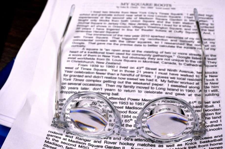 John Contrata's glasses, 81, rest on a story, in a writing group, at the Bethel Senior Center, on Monday, Dec.28,2009. Photo: Michael Duffy / The News-Times