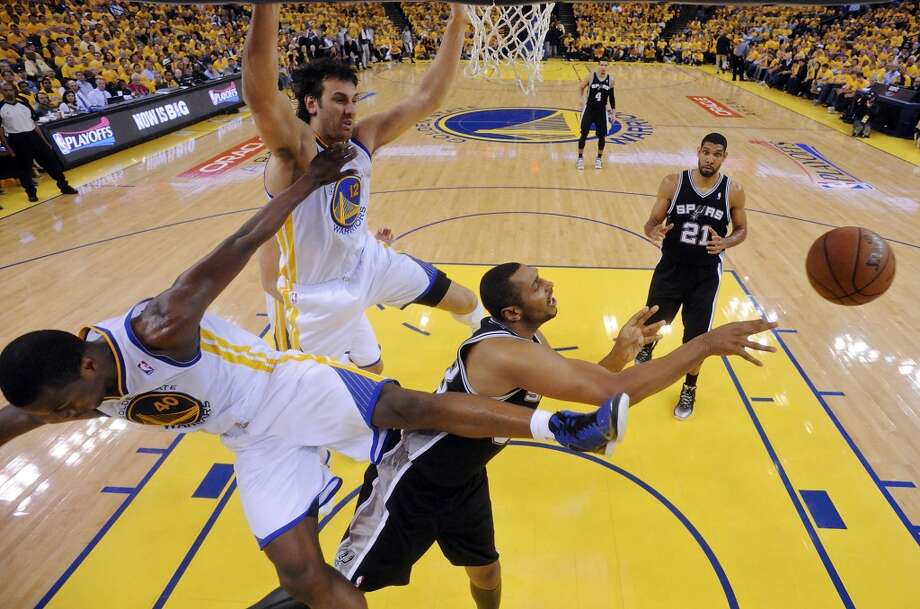 San Antonio Spurs' Boris Diaw passes between Golden State Warriors' Harrison Barnes and Golden State Warriors' Andrew Bogut during first half action of Game 6 in the NBA Western Conference semifinals Thursday May 16, 2013 at Oracle Arena in Oakland, CA. Barnes was injured on the play.