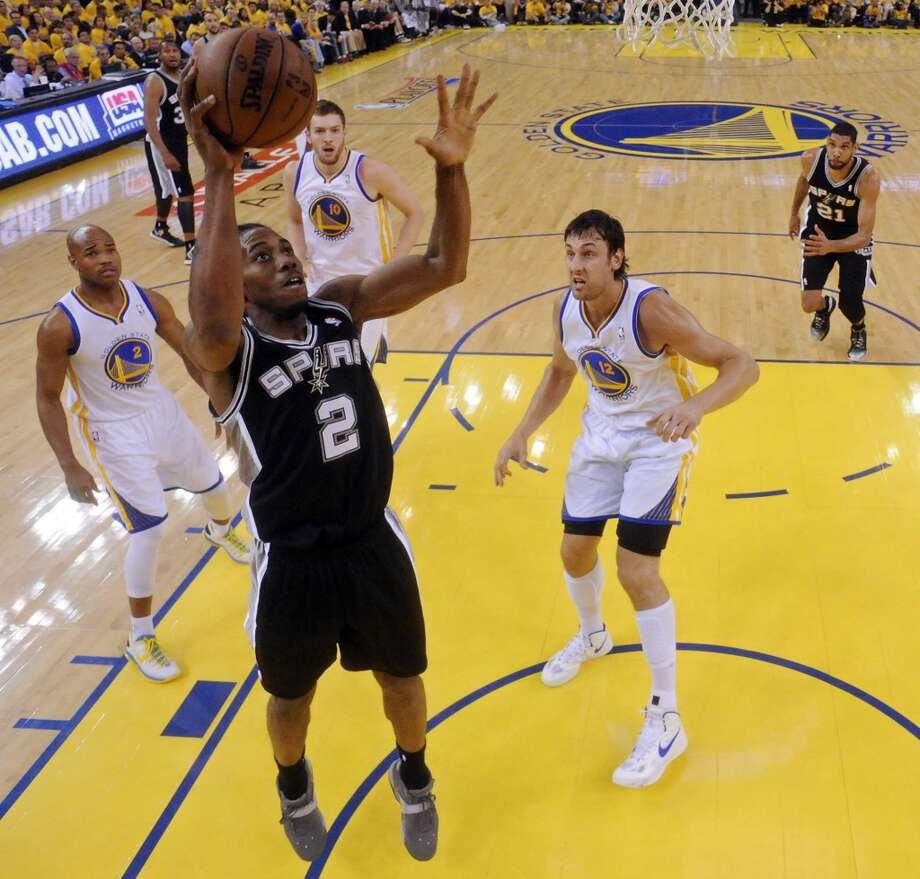 San Antonio Spurs' Kawhi Leonard shoots between Golden State Warriors' Jarrett Jack and Golden State Warriors' Andrew Bogut during first half action of Game 6 in the NBA Western Conference semifinals Thursday May 16, 2013 at Oracle Arena in Oakland, CA.