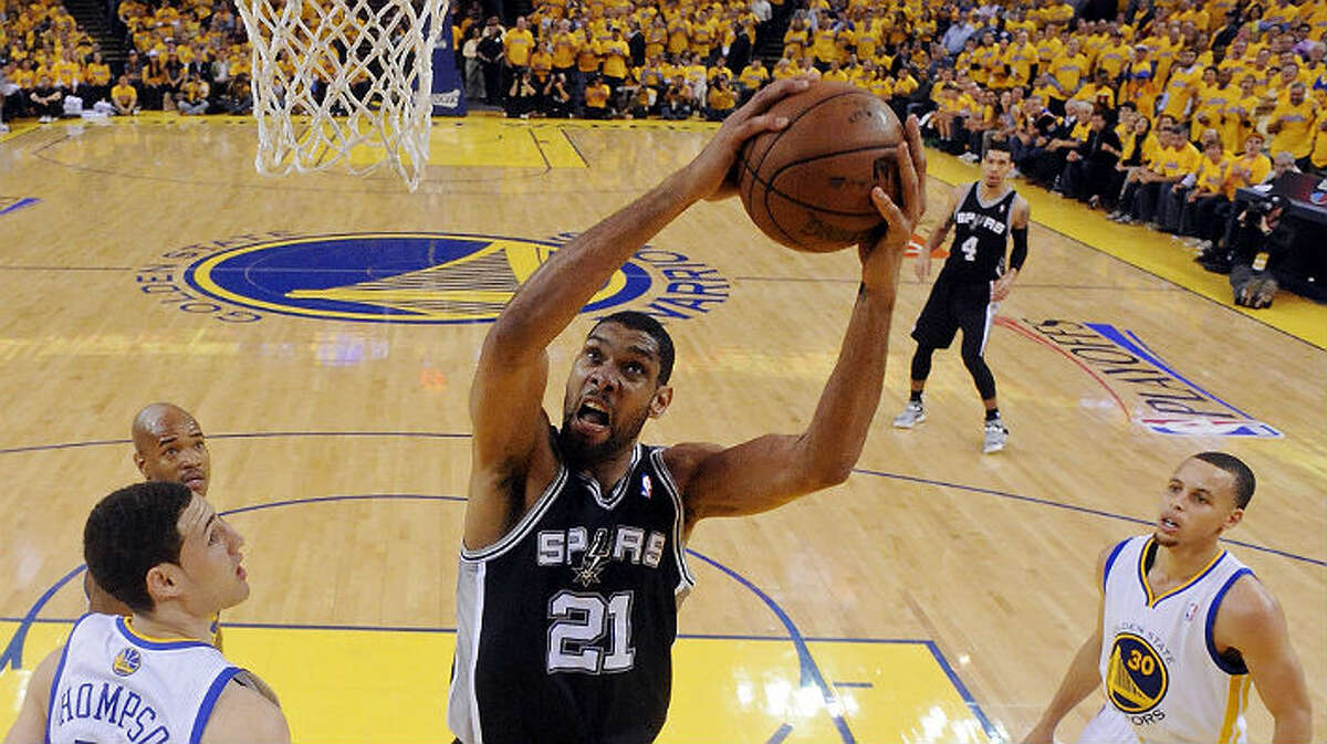Tim Duncan, going in for a shot between the Warriors' Klay Thompson (from left), Jarrett Jack and Stephen Curry, led the Spurs with 19 points but sat out the final minutes of the game. Edward A. Ornelas / San Antonio Express-News