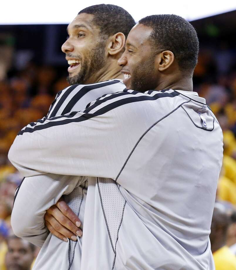 San Antonio Spurs' Tim Duncan is hugged by San Antonio Spurs' Tracy McGrady during second half action of Game 6 in the NBA Western Conference semifinals against the Golden State Warriors Thursday  May 16, 2013 at Oracle Arena in Oakland, CA. The Spurs won 94-82.