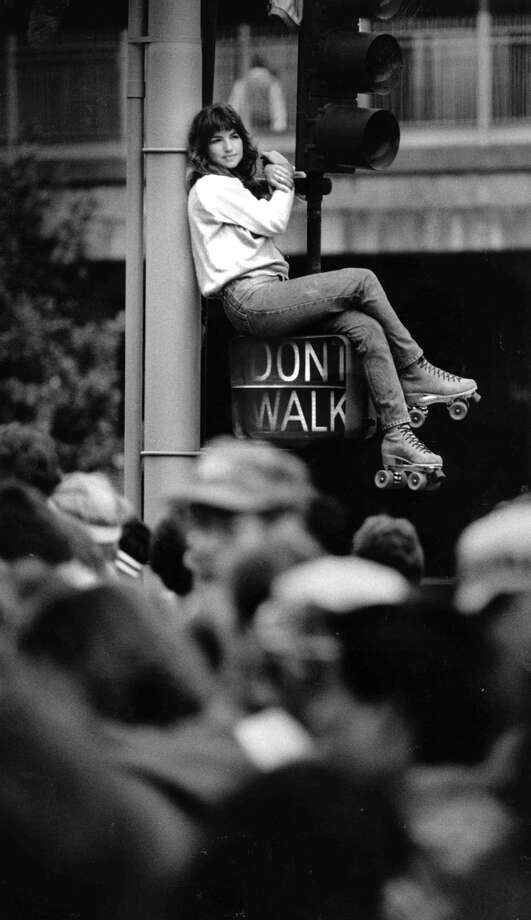 This woman is reaching a new height to see the crazies running in the Bay to Breakers near the start at Howard St. and Fremont St. during the 1986 Bay to Breakers. Photo: Steve Ringman, The Chronicle / ONLINE_YES