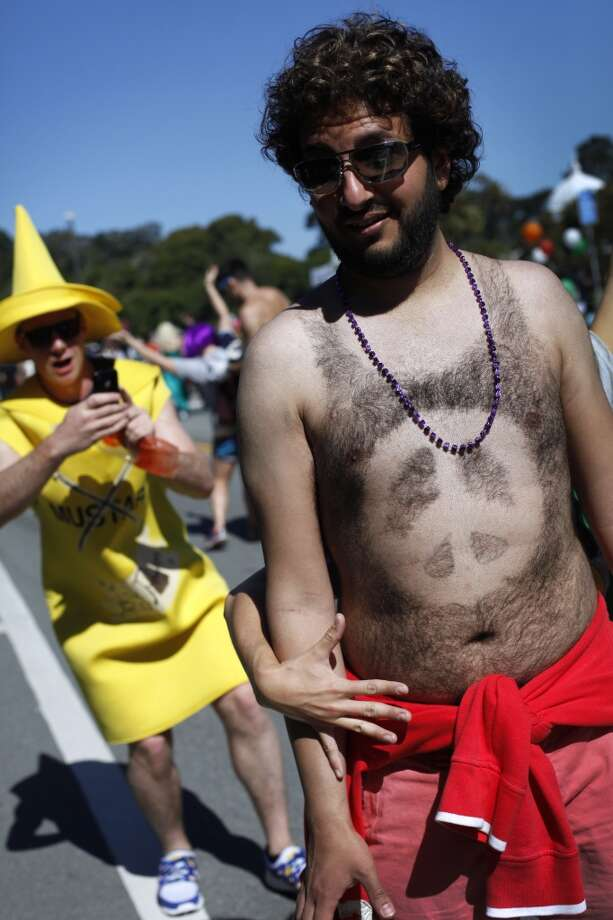 Norm (no last name given), of Campbell, gets surprised by a stranger grabbing him as a man in a mustard costume takes a photo of the #12 shaved into the hair jersey on his back during the annual Bay to Breakers run in 2012. Photo: Sarah Rice, Special To The Chronicle