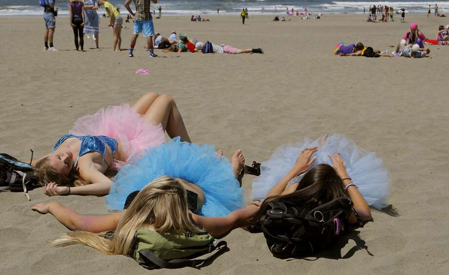 Three young women in tutus resting on Ocean Beach during  the 101st Bay to Breakers foot race in 2012.