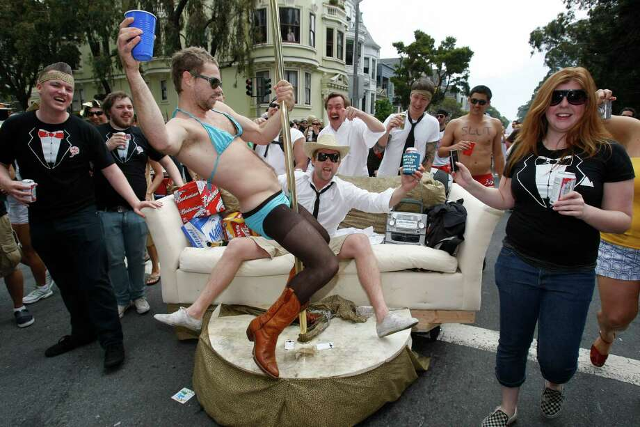 Ian Aldous of San Francisco, Calif., sat on a rolling couch inviting pole dancers to entertain him. Ben Damron accepted the invitation as they traveled on Fell Street near Golden Gate Park during the 97th annual race.  Photo: Michael Maloney, The Chronicle / The Chronicle