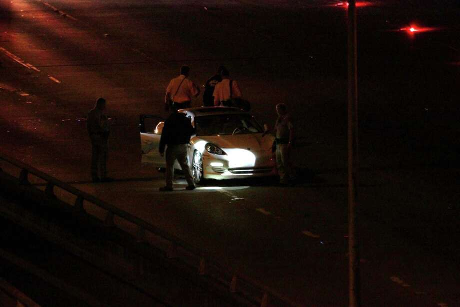 The CHP investigates a Porsche raked with bullets on Interstate 880 in downtown Oakland Thursday night. Two victims died at the scene. Photo: ;, Courtesy Of Tamara De Jong