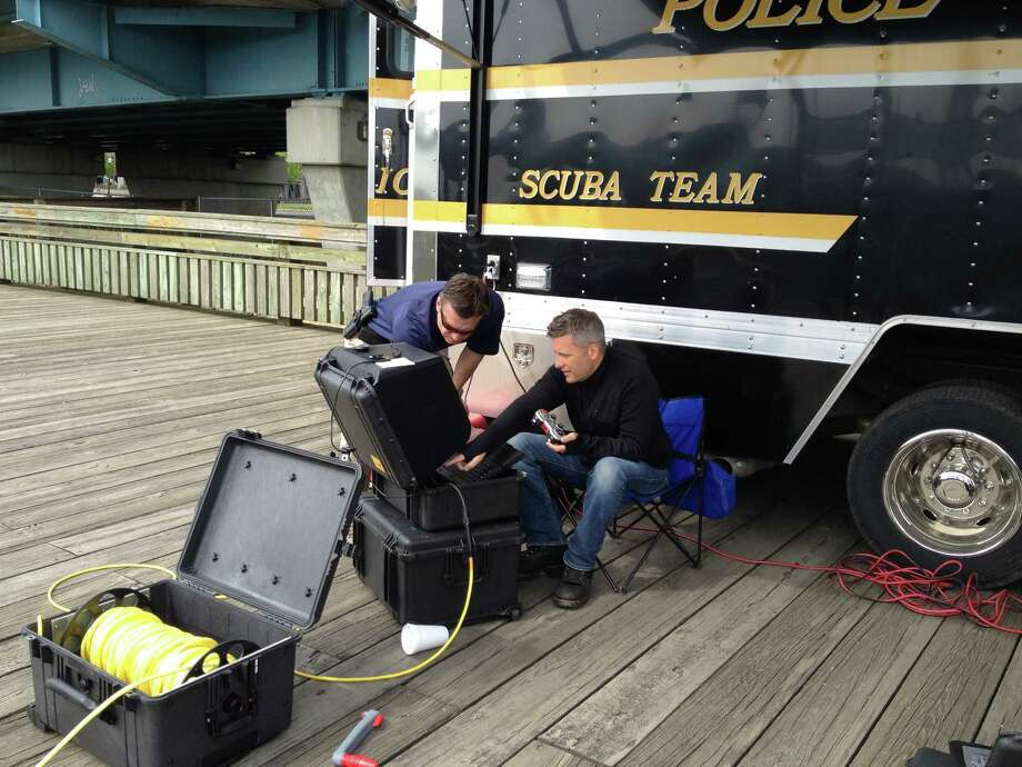 Members of the Bridgeport police SCUBA team train with the department's new remote-controlled submersible. The $125,000 device uses sonar, GPS and video to locate object under water. Photo: Connecticut Post