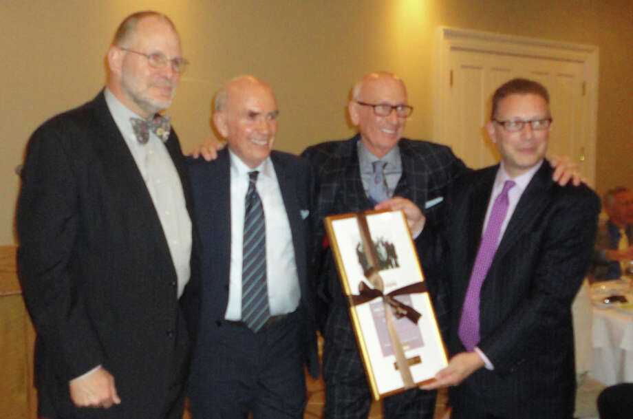The Mitchell family, owners of Mitchells of Westport, was honored by Operation Hope of Fairfield on Thursday night. Jack Mitchell, second from left, and Bill Mitchell, standing to the right of his brother, were called to the front of the Patterson Club banquet hall to receive an award from Jeffrey Ruden, far right, chairman of the Operation Hope gala, and Michael Rosten, far left, chairman of the non-profit agency's board of directors. Photo: Meg Barone / Westport News contributed