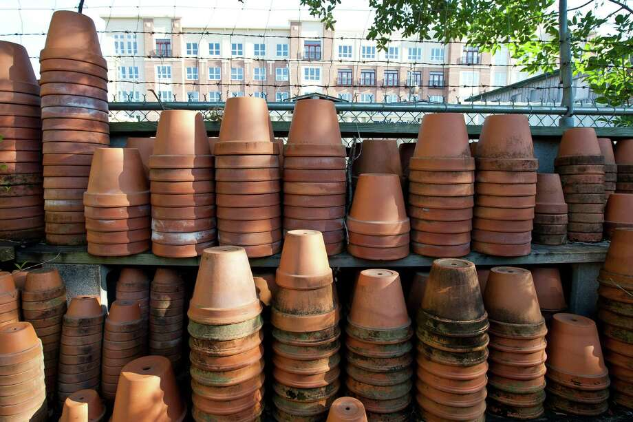 Pots that are stacked and ready for relocation stand on the south wall of the Garden Gate property, across the way from a new mix use building, Tuesday, May 7, 2013, near Rice Village in Houston. The Garden Gate, will come to a close after 20-years. ( Nick de la Torre / Chronicle ) Photo: Nick De La Torre, Staff / © 2013 Houston Chronicle