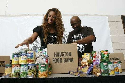 Houston recording artist, Beyonce, works with Rudy Rasmus, pastor of St. John's Downtown Church putting non-perishable food items in a box for the Houston Food Bank that will be given to those in need in the Houston area, before Beyonce's concert at the Toyota Center Saturday, July 14, 2007, in Houston.