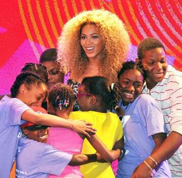 Here, children embrace Beyoncé at a New York City Target event in June, two months before she announced her pregnancy. (Stephen Lovekin/Getty Images)